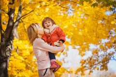 Mother and her baby have fun in the autumn park Stock Photo