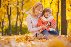 Mother and her baby have fun in the autumn park Royalty Free Stock Image