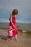 Mother with her baby  having fun on the beach. Portrait of young mother with her baby  having fun on the beach Stock Photos