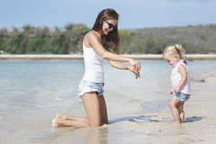 Mother with her baby having fun on the beach Stock Photos