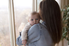 Mother with her baby at home close to  window Royalty Free Stock Image