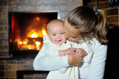 Mother with her baby near the fireplace at home Royalty Free Stock Photo
