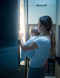 Mother with her baby opening refrigerator at late night Stock Photos