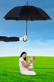 Mother and her baby playing under umbrella at field Stock Photography