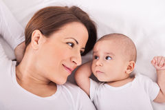 Mother with her baby relaxing on bed Stock Photo