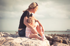 Mother and her baby sitting together on the beach coast during sunset and looking into the distance. Stock Images
