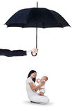 Mother and her baby sitting under umbrella. Image of young happy mother holding her little daughter in the studio under umbrella. Life and family insurance Royalty Free Stock Images