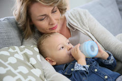 Mother with her baby son drinking from baby bottle Royalty Free Stock Photo