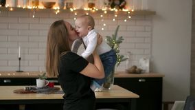 Mother and her baby son having fun and playing at home. Little kid 2 years old play with his mom arms at home near a big