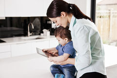 A mother with her baby son, looking at a digital tablet Stock Images