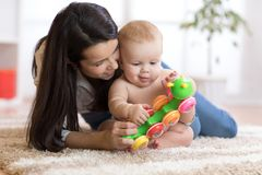 Mom and her baby son play with toy in cosy children room. Mother and her baby son play with toy in cosy children room royalty free stock photos