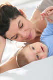 Mother and her baby son resting on the bed Royalty Free Stock Images