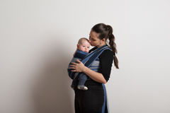 Mother with her baby son in sling, kissing him. Studio shot. Beautiful young mother with her baby son in sling, kissing him on head. Studio shot on white Royalty Free Stock Image