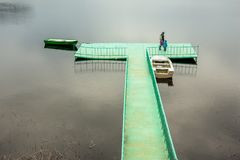 A metal wharf with two small boats and people. Russia stock photography