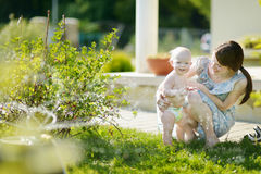 Mother and her baby under a sprinkler Stock Image