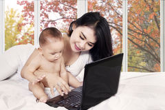 Mother and her baby using laptop Stock Images