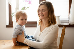 Mother with her beautiful baby boy at the kitchen. Happy childhood and parenting Royalty Free Stock Image