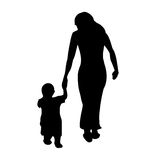 A mother with her child. A mother walking with her little child silhouette Royalty Free Stock Image