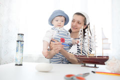Mother and her child boy making model ship. Stock Photos