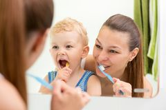Mother and child brushing their teeth toothbrushes front of the mirror in the bathroom stock photos