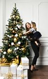 Mother with her child daughter celebrating near Christmas tree royalty free stock photo