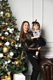 Mother with her child daughter celebrating near Christmas tree royalty free stock photography
