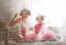 Mother and her child daughter. Funny family! Mother and her child daughter girl with a paper accessories. Mother and daughter preparing for a party and having Stock Photography