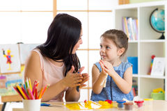 Mother and her child daughter moulding together from plasticine snail at home interior Stock Photography