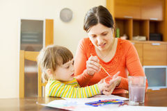 Mother and her child drawing on paper with hands and watercolor Royalty Free Stock Photography
