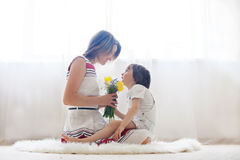 Mother and her child, embracing with tenderness and care. Child  giving mother flowers. Mother day concept, happiness and love Stock Image