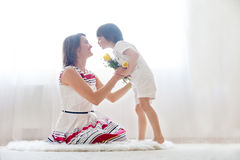 Mother and her child, embracing with tenderness and care. Child  giving mother flowers. Mother day concept, happiness and love Royalty Free Stock Photo