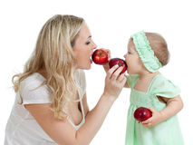 Mother and her child feed each other by red apples Stock Images
