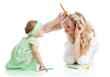 Mother and her child fun games with color pencils. Mother and her child fun games with colored pencils Royalty Free Stock Photo