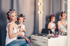 Mother and her child girl are doing your makeup and having fun Stock Photography