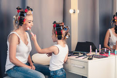 Mother and her child girl are doing your makeup and having fun Royalty Free Stock Image