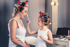 Mother and her child girl are doing your makeup and having fun Royalty Free Stock Photos