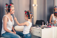 Mother and her child girl are doing your makeup and having fun Stock Photos