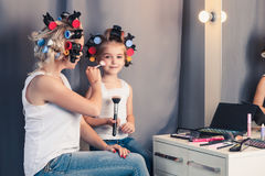 Mother and her child girl are doing your makeup and having fun Stock Image