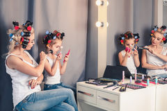 Mother and her child girl are doing your makeup and having fun Stock Photo