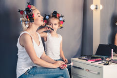 Mother and her child girl are doing your makeup and having fun n Royalty Free Stock Photo