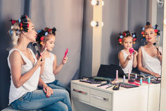 Mother and her child girl are doing your makeup and having fun n Stock Photos
