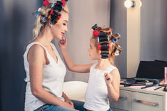 Mother and her child girl are doing your makeup and having fun n Stock Photo