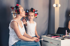 Mother and her child girl are doing your makeup and having fun n Royalty Free Stock Images