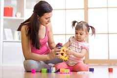Mother and her child playing with colorful logical sorter toy. Mother and her child girl playing with colorful logical sorter toy Royalty Free Stock Images