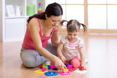 Mother and her child playing with colorful logical sorter toy. Mother and her child girl playing with colorful logical sorter toy royalty free stock image