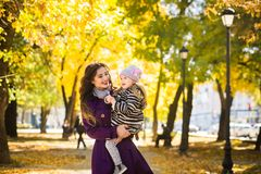 Mother and her child girl playing together on autumn walk in nature outdoors. royalty free stock photography