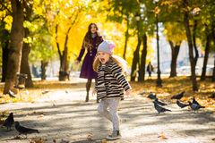 Mother and her child girl playing together on autumn walk in nature outdoors. royalty free stock photo