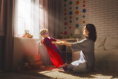 Mother and her child. Girl playing together. Girl in an Superman's costume. Happy loving family having fun Royalty Free Stock Image