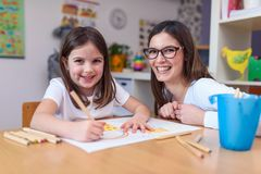 Mother with her child having creative and fun time drawing. Kindergarten teacher helping kid stock photos