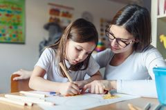 Mother with her child having creative and fun time drawing. Kindergarten teacher helping kid royalty free stock photography